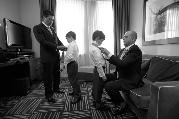 Father and groomsmen tying little Ring Bearer ties before the wedding ceremony - Photo by The Mamones