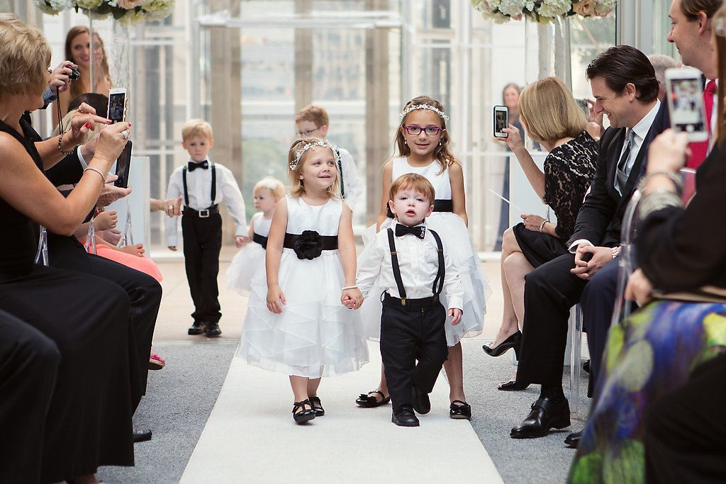 Flower Girls and Ring Bearers holding hands and walking down wedding ceremony aisle - Photo by Joshua Aull Photography